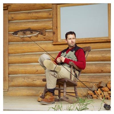 تصویر با کیفیت مرد در حال استراحت در کنار کلبه و روی صندلی