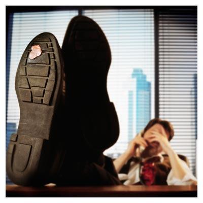عکس مرد خسته لم داده به صندلی با آدامس چسبیده کف کفش