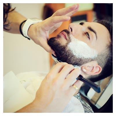 تصویر استوک از مردی در حال پیرایش صورت و ریش در آرایشگاه مردانه