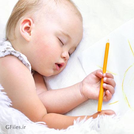 تصویر استوک با کیفیت از دختر بچه خوابیده در کنار کاغذ نقاشی