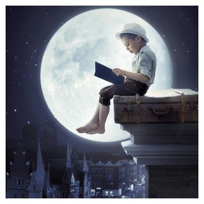عکس فانتزی و خلاقانه با موضوع پسربچه در حال مطالعه کتاب در قرص ماه
