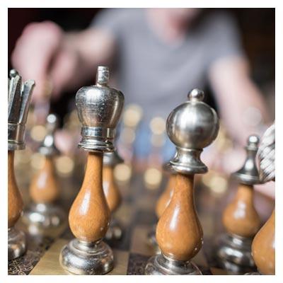 عکس مهره های زیبای شطرنج با پایه فلزی و پس زمینه بازیکن حریف