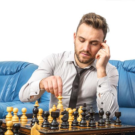 عکس مرد جوان متفکر در حال بازی شطرنج با خودش در منزل در کنار مبل آبی