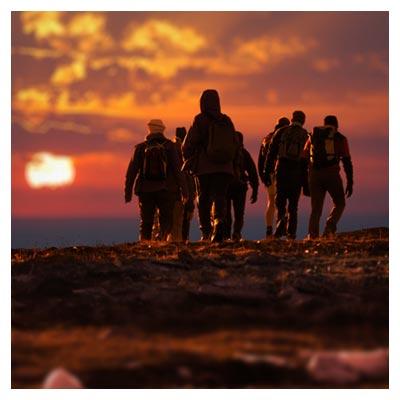 تصویر گروهی متشکل از مردان صحرا نورد در حال عظیمت به سمت بیابان در زمان غروب آفتاب