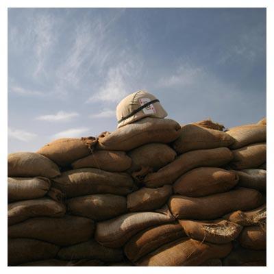 تصویر سنگرهای جنگ ساخته شده با کیسه های شنی، با نمای آسمان صاف و یک کلاه سرباز