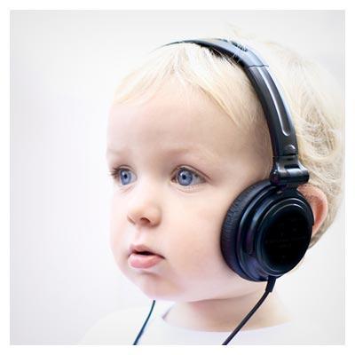 تصویر کودک مو طلایی در حال گوش دادن به موزیک توسط یک هدفون