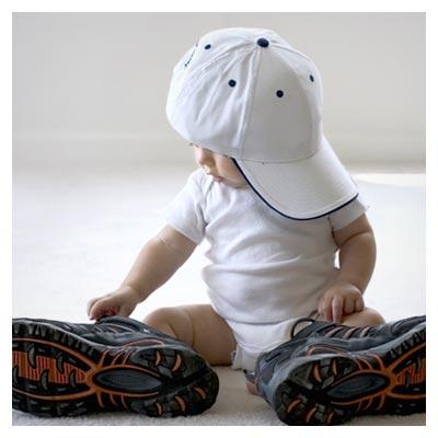 تصویر کودک پسر نشسته با لباس سفید، با کلاه و کتانی بسیار بزرگ به فرمت jpg