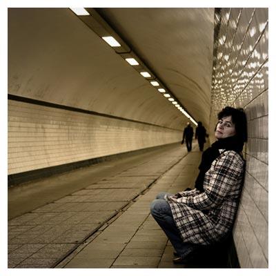 عکس یک زن تنها و منتظر تکیه زده بر دیوار در ایستگاه مترو