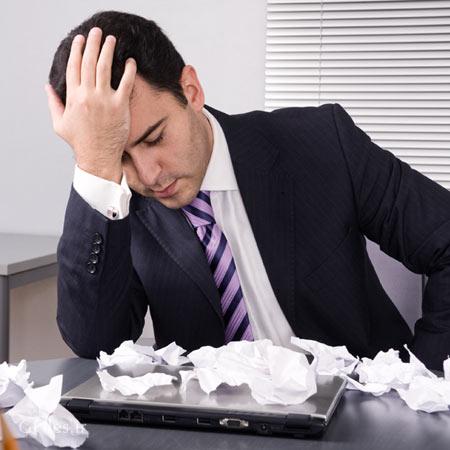 عکس یک کارمند ناراحت و کسل بعد از مچاله کردن تعدادی کاغذ به فرمت jpg