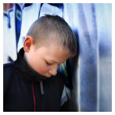 عکس پسربچه بور با کاپشن کنار دیوار به حالت ناراحت و در فکر فرو رفته