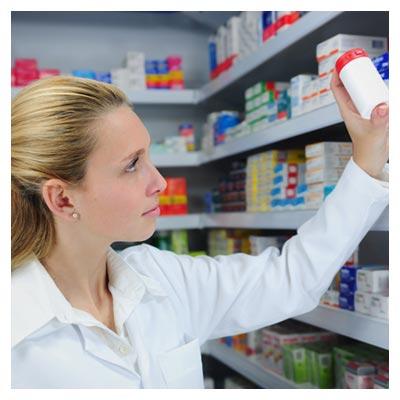 عکس خانم دارو فروش سفید پوش در حال برداشتن دارو از روی قفسه داروها
