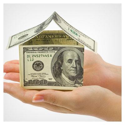عکس یک خانه ساخته شده با چند اسکناس دلار در دست شخص