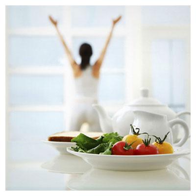 عکس خانم خوشحال در جلو پنجره در کنار میز صبحانه شامل گوجه فرنگی و کاهو