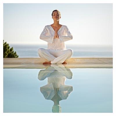 عکس خانم با چشمان بسته در حال ورزش یوگا در طبیعت در کنار آب