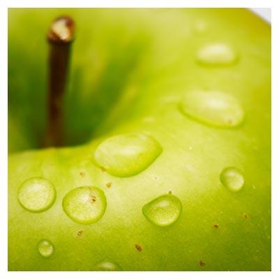 تصویر قطره های آب باران جاری بر روی بخشی از یک سیب سبز