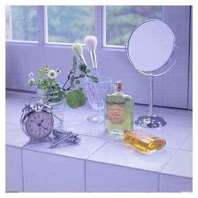 عکس آینه و ساعت رومیزی در کنار پنجره با پد آرایشی و عطر