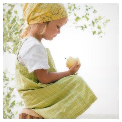 عکس دختر کوچک در حالت نشسته با یک سیب زرد در دست