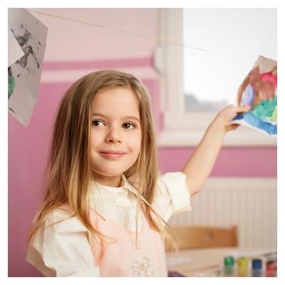 عکس لبخند دختر بچه در کنار نقاشی آویزان با طناب با گیره لباس
