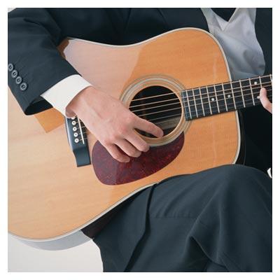 عکس گیتار در دستان یک مرد با کت و شلوار در حال نواختن گیتار