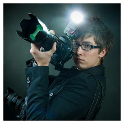 ژست یک عکاس جوان در حالت عکسبرداری با دوربین پیشرفته