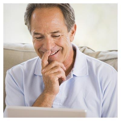 عکس مرد میانسال در حال کار کردن با تبلت بر روی مبل و لبخند زدن