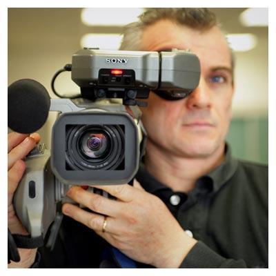 عکس دوربین فیلمبرداری پیشرفته در دست یک مرد فیلمبردار