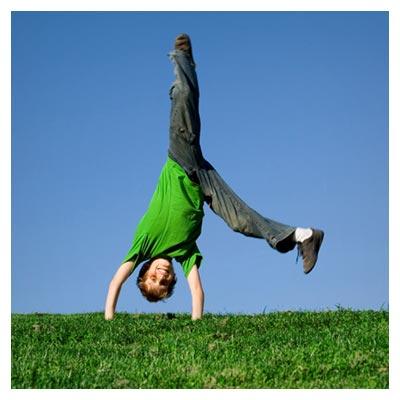 ایستادن پسر بچه شاد و پر انرژی بر روی دو دست در طبیعت