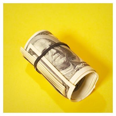 عکس اسکناس دلار لوله شده قرار گرفته بر روی زمینه زرد