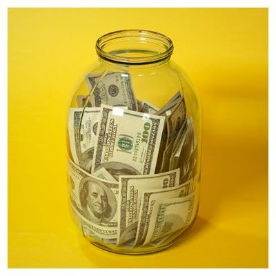 ظرف شیشه ای حاوی اسکناس های دلار بر زمینه زرد رنگ