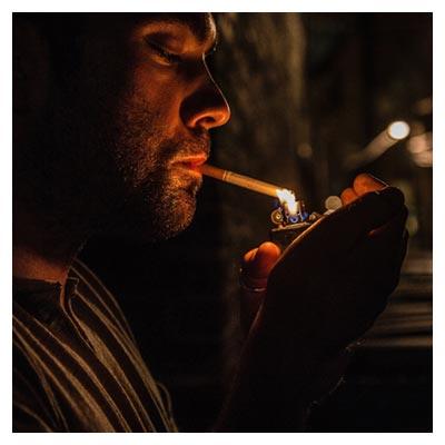 عکس سیگار روشن کردن مرد در کوچه خلوت و تاریک