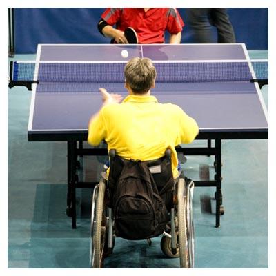 عکس بازی پینگ پنگ معلولان بر روی ولچر در کنار میز تنیس