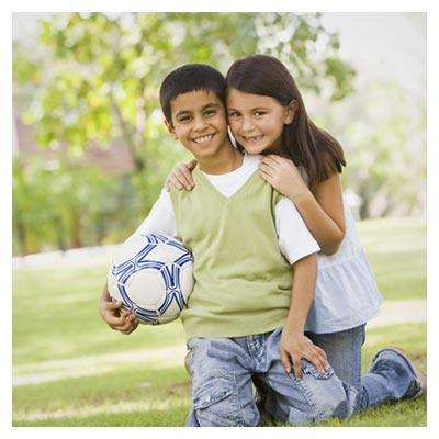 عکس خواهر و برادر مهربان در حال لبخند در یک پارک کنار توپ فوتبال