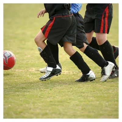 عکس توپ نارنجی فوتبال بر روی زمین چمن در کنار پای بازیکنان سیاهپوش