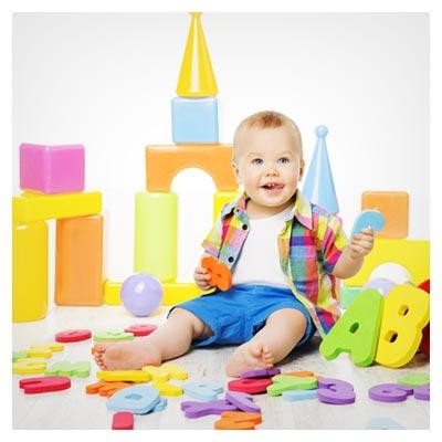 عکس بازی کردن کودک خندان با اسباب بازی حروف الفبای لاتین