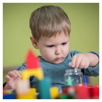 عکس کنجکاوی و جدیت کودک پسر در حال بازی