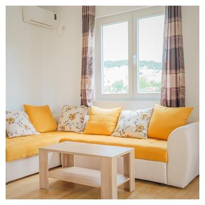 عکس دکوراسیون داخلی اطاق نشیمن با پنجره و مبلمان زرد و کرمی