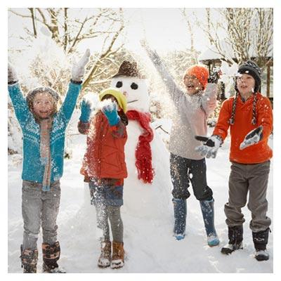عکس خانواده چهار نفره در حال برف بازی در کنار آدم برفی