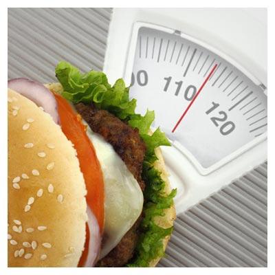 عکس یک ساندویچ همبرگر در حال وزن کردن خود، به مفهوم چاقی و اضافه وزن