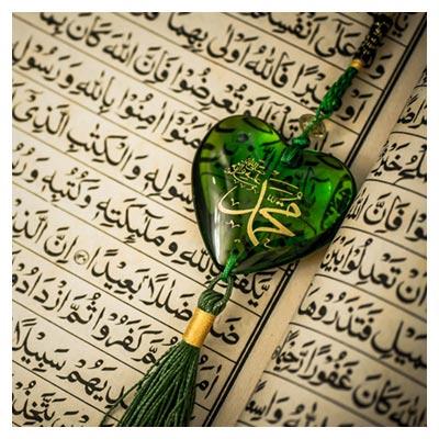 عکس قرآن باز با یک نشان قلب مانند سبز رنگ با نوشته ی محمد(ص)