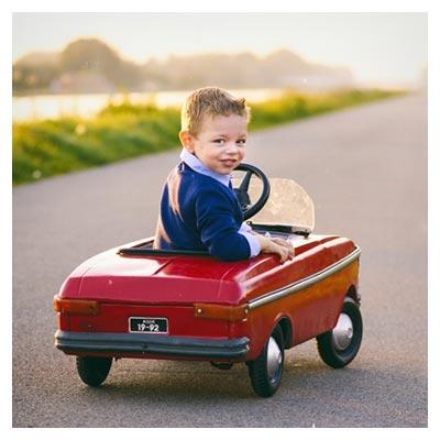 عکس پسربچه کوچک سوار ماشین اسباب بازی قرمز رنگ در خیابان
