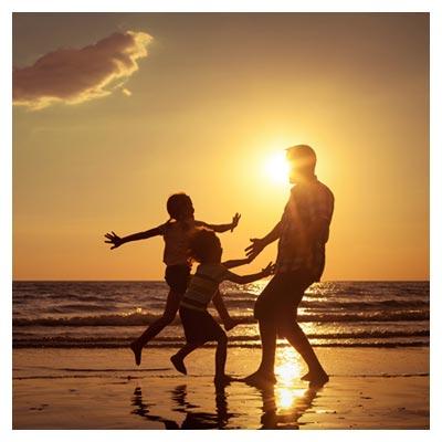 عکس بازی کردن پدر با دو فرزند در ساحل دریا در زمان غروب خورشید
