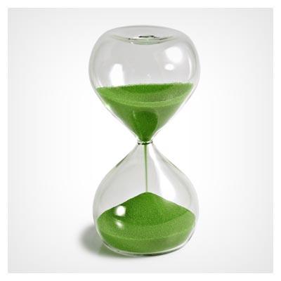 عکس شن سبز در یک ساعت شنی شیشه ای بزرگ