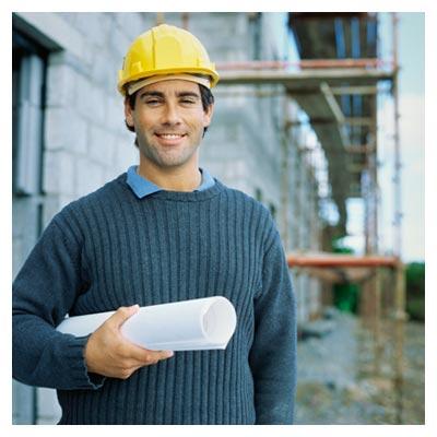 عکس مهندس معماری با کلاه زرد و نقشه ساختمان در حال لبخند