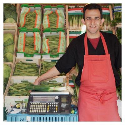 دانلود تصویر مغازه سبزی فروشی و مرد سبزی فروش مهربان کنار تره و کلم