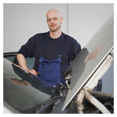 دانلود عکس مرد تعمیرکار مهربان و خندان در کنار خودروی درحال تعمیر با کاپوت باز