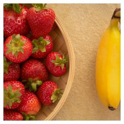 دانلود عکس ظرف پر از توت فرنگی و یک جفت موز متصل به هم با فرمت jpg