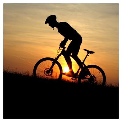 دانلود عکس رایگان بالا رفتن دوچرخه سوار در زمان غروب آفتاب از یک سربالایی