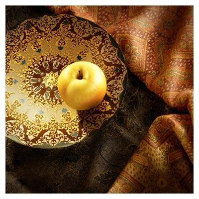 دانلود تصویر هنری پارچه ها و ظرف سنتی قدیمی و یک سیب زرد با فرمت jpg