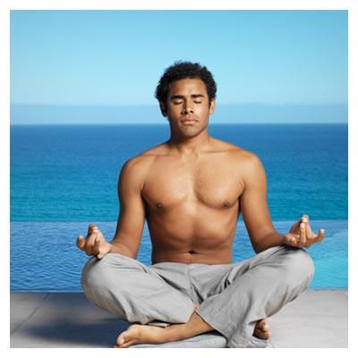 دانلود تمرین یوگا در کنار دریا توسط مرد جوان بدون پیراهن با چشمان بسته به حالت چهارزانو